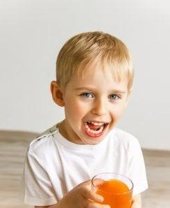 Junge lächelt mit seinem Saft in der Hand. Kleinkinder sind oft betroffen von Pilz im Mund.