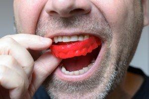 Der Mann steckt sich den roten Mundschutz beim Hockey in den Mund.