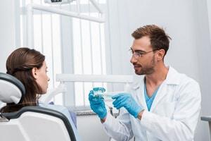 Zahnarzt setzt Patientin Zahnspange ein