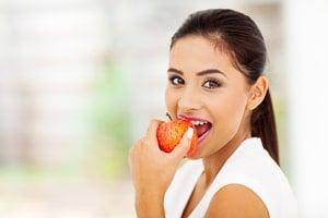 Junge Frau mit gesunden Zähnen isst Apfel.
