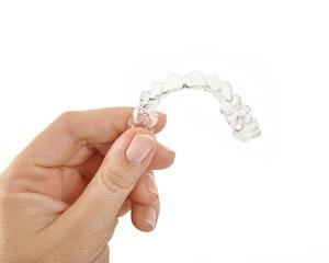 Frau hält unsichtbare Zahnspange in die Luft