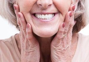 Ältere Frau lächelt mit weißen Zähnen