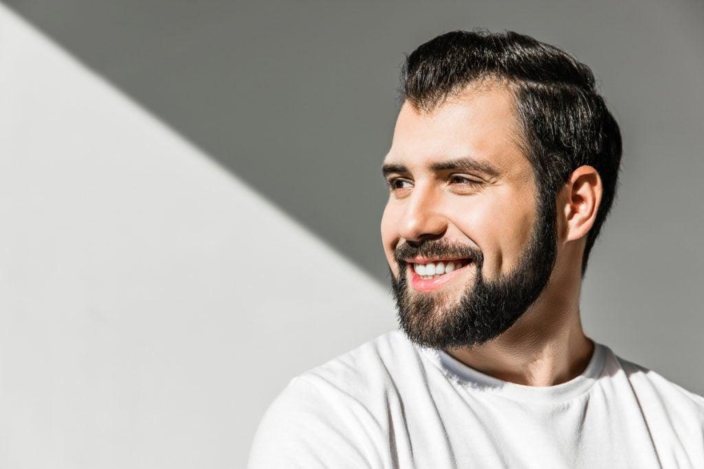Junger Mann lächelt mit weißen Zähnen