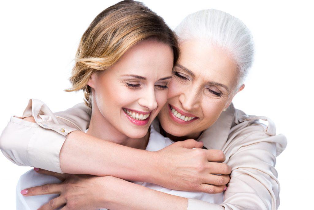 Junge Frau und ältere Frau lächeln und umarmen sich