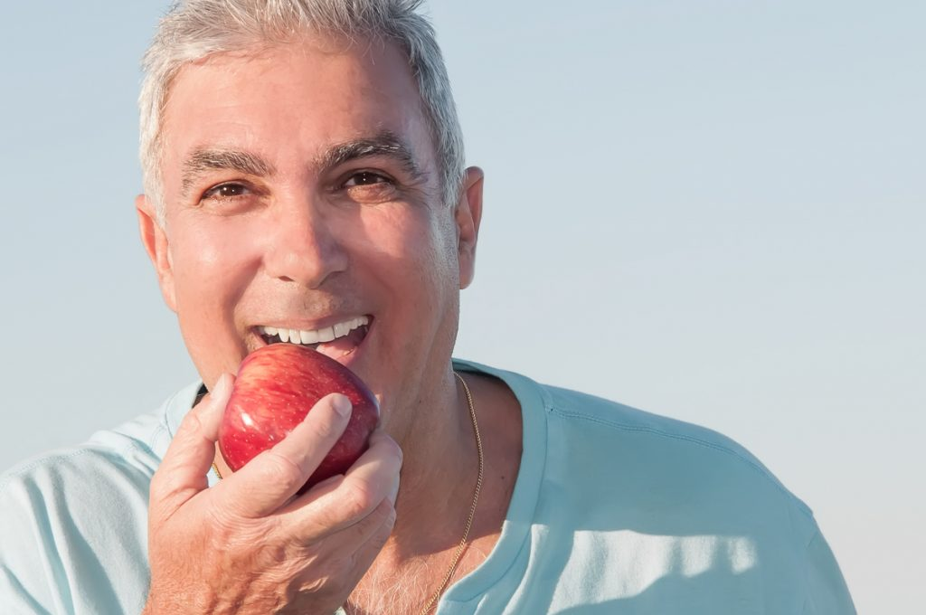 Mann beißt in einen Apfel und lacht