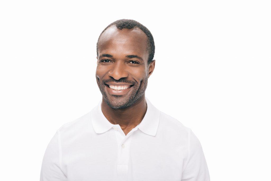 Mann lächelt mit weißen Zähnen