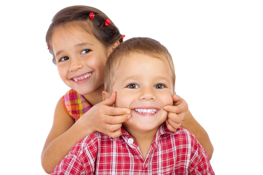 Zwei Kinder lächeln mit weißen Zähnen