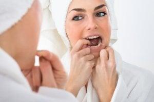woman using string floss to clean teeth