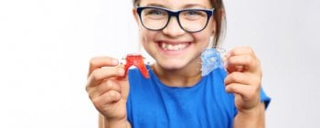 Grinning girl holding two dental retainers