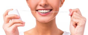 woman with braces holding dental floss