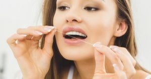 woman cleaning between teeth