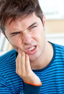 man with painful tooth