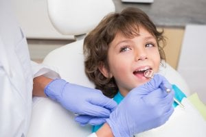 dentist checking boy's teeth