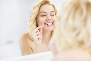 Mujer pasandose el hilo dental en casa