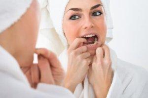 mujer usando el hilo dental