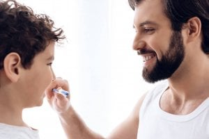 father holding kid's toothbrush