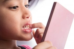 boy checking teeth for fluorosis