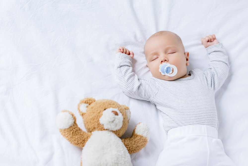 Child sleeping with a pacifier in mouth