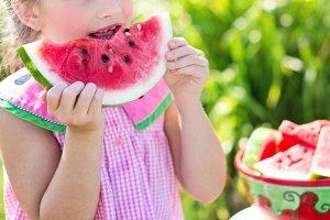 enfant mange un fruit, bénéfique pour la perlèche et inflammation de la bouche