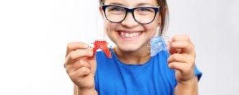 petite fille souriante et portant des lunettes tenant deux appareils dentaires de type faux-palais dans ses mains